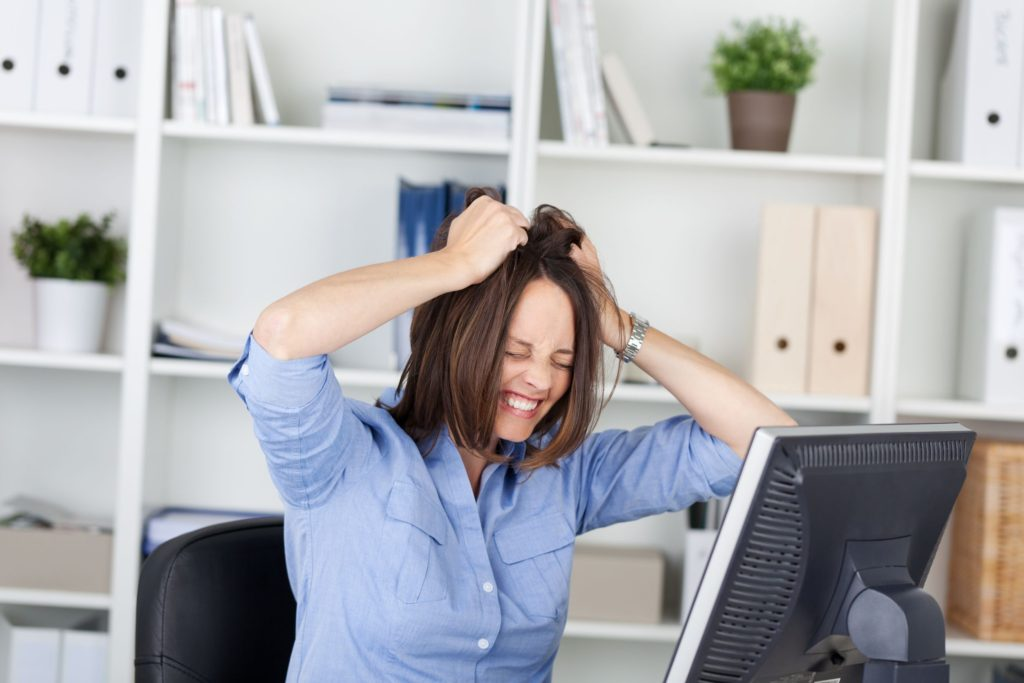 21266037 - irritated businesswoman pulling her hair while sitting in office